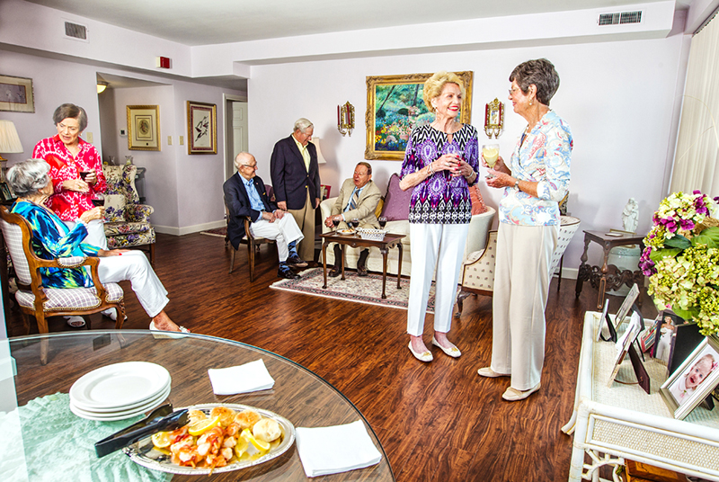 A group of senior women and men socialize in a nice living area