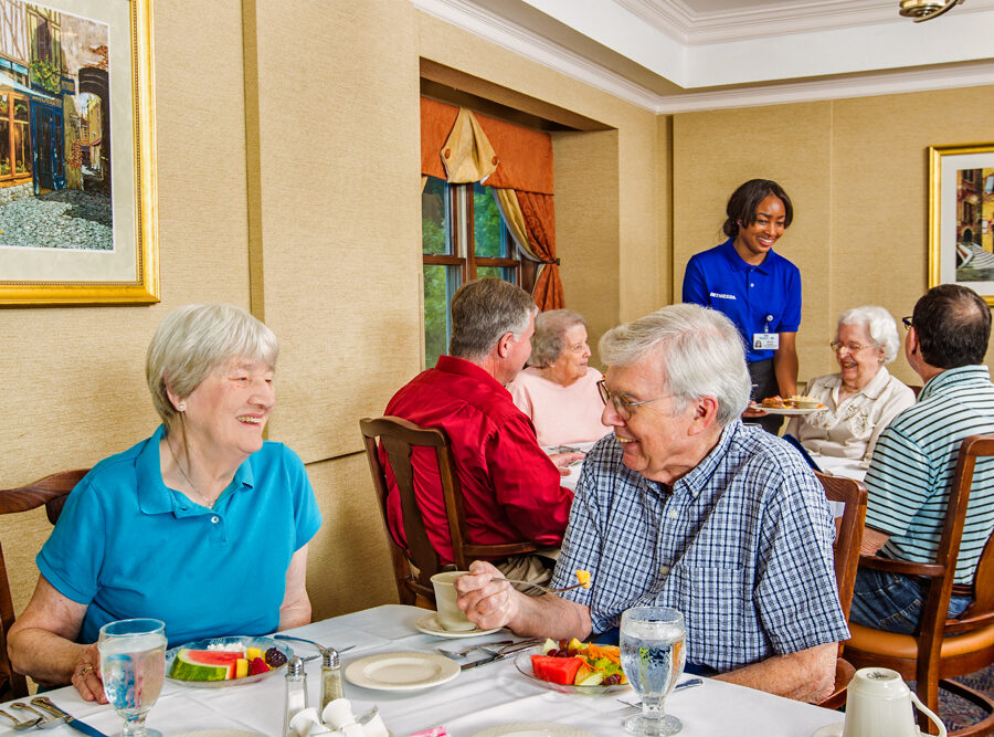 several seniors dine in a nice looking restaurant with a server attending them