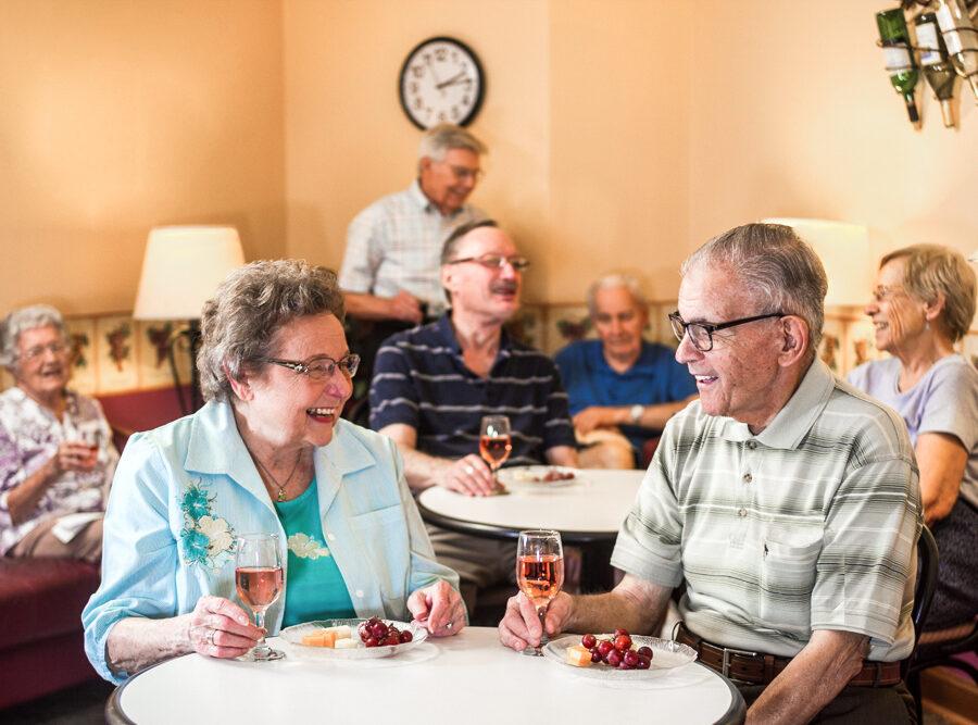 Several seniors enjoy social hour at Bethesda Gardens with wine