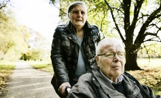 A senior woman pushing her husband in a wheel chair, one of the demands of caregiving