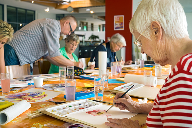 senior women and men paint at Bethesda Charless Village, with an instructor helping