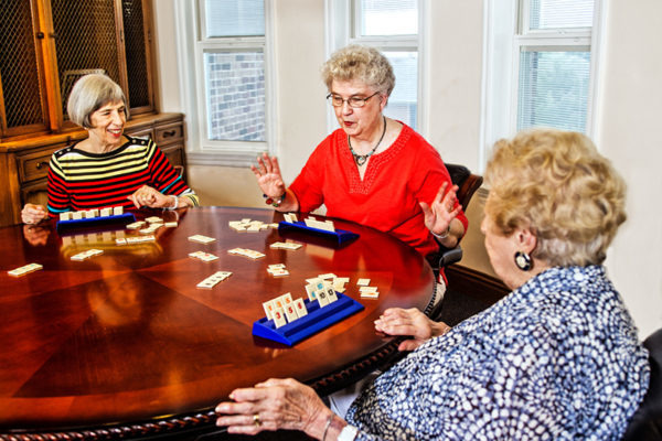 three senior women play dominos together at a round wooden table