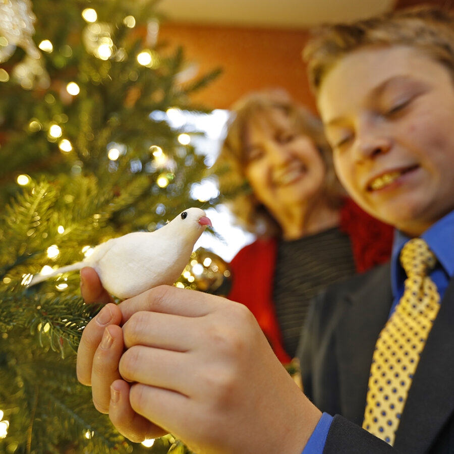 A young boy holds a Hope Dove ornament while an older woman smiles behind him by the Christmas tree