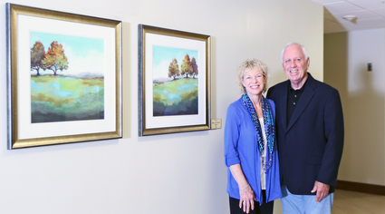 A man and woman posing in front of artwork that they contributed in the Lasting Impression program