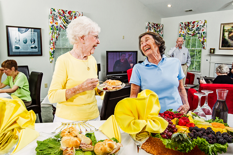 Two senior women laugh over breakfast