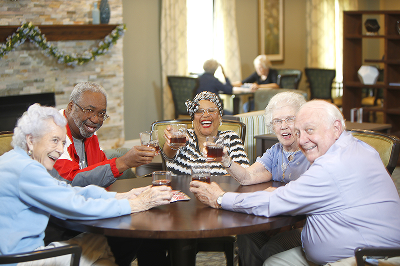A group of five seniors raise their glasses toward the camera as they cheers in a comfortable living area around a round table