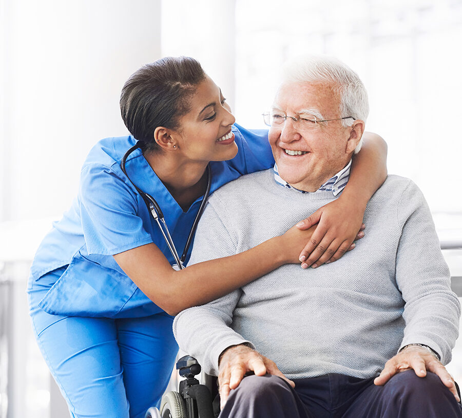 young female nurse hugging the shoulders of a senior man in a wheelchair