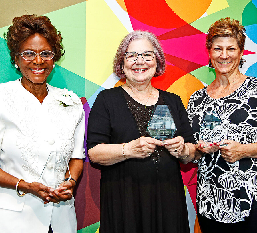 three older women hold an award in front of a colorful wall
