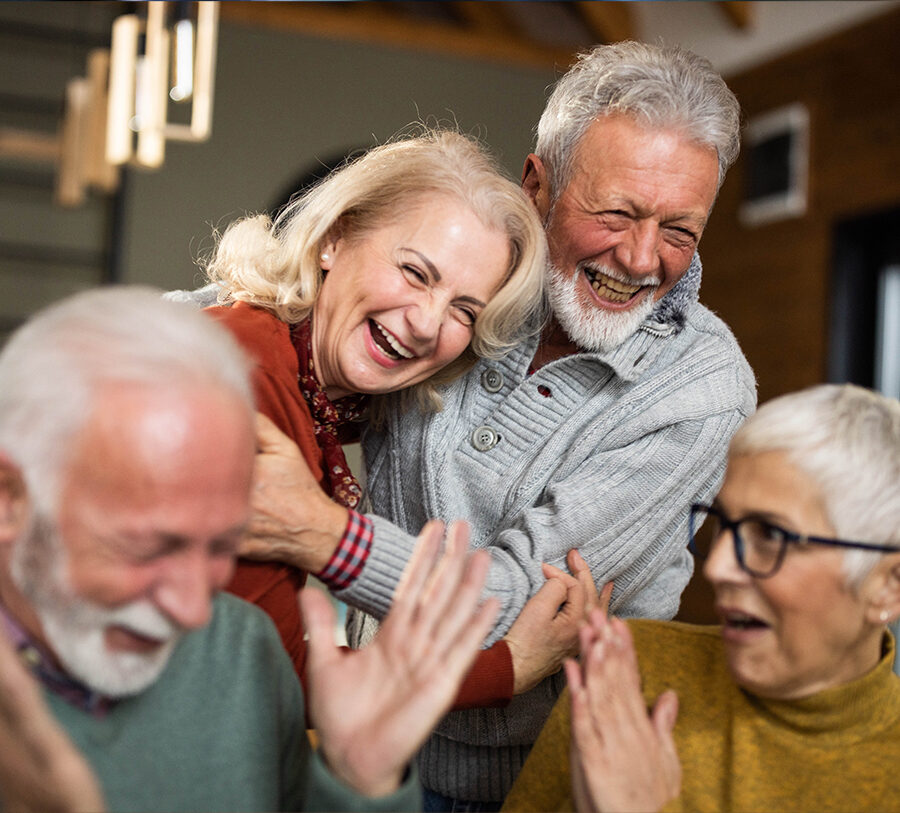Group of four senior friends - two men and two women - laugh together at Barclay House