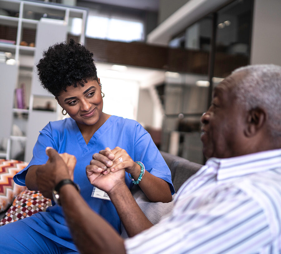 A young Care in Your Home female nursing professional offers support to a senior gentleman in his living room