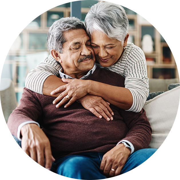 Senior woman hugs senior man from behind as he is seated on a couch