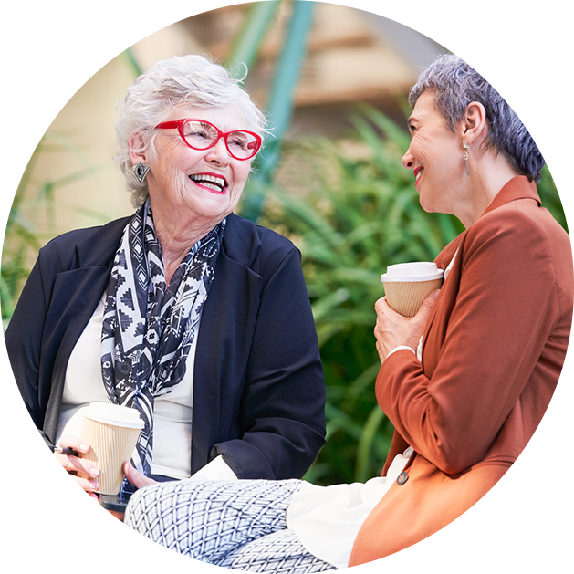 Two senior women chat and laugh outside over coffee