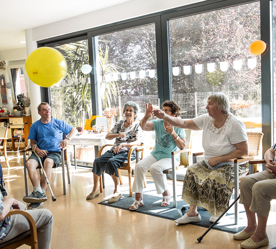 A group of seniors find a community where they sit in a circle of chairs and laugh as they play a game