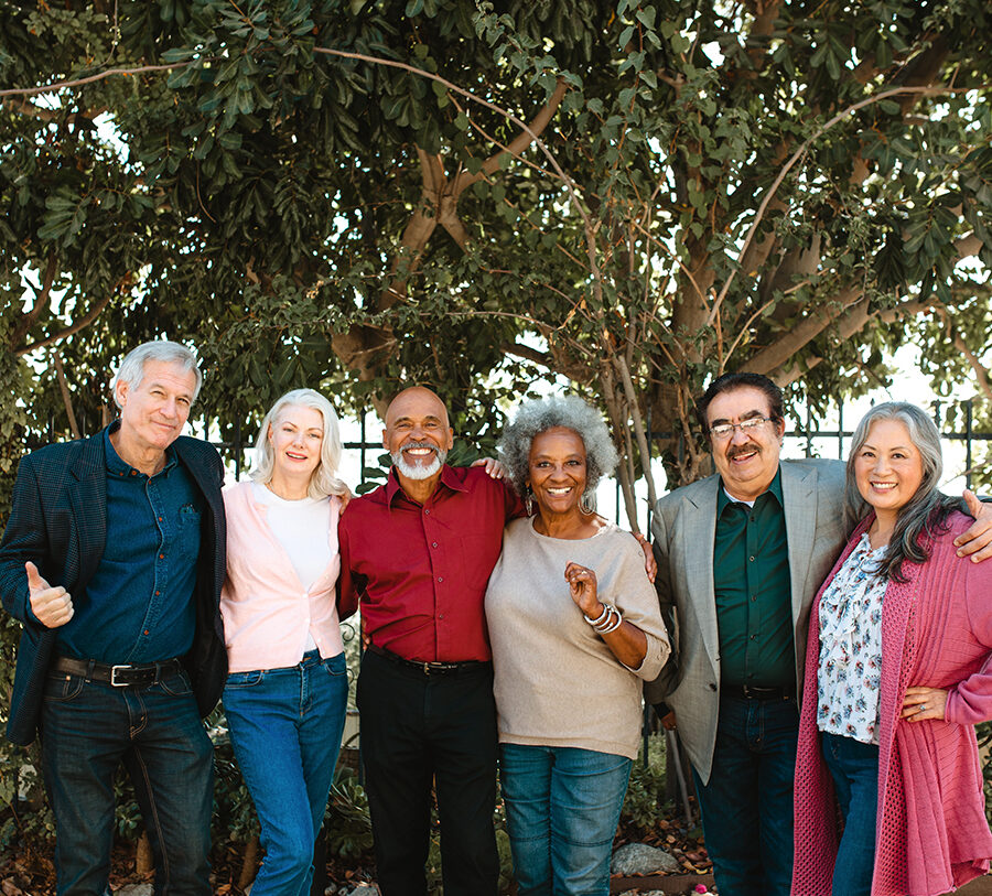 A group of six senior men and women pose for a photo in front of a tree