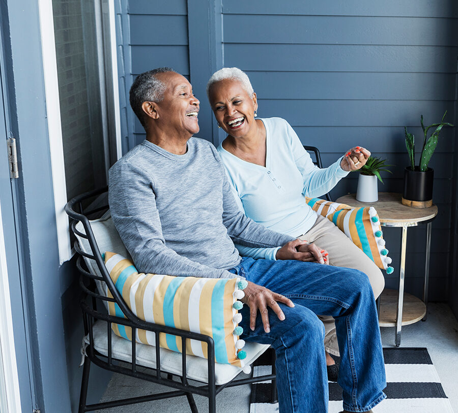 Senior man and woman chat and laugh on a porch chair