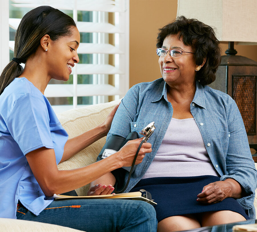 A senior woman receives home health care from a young female nurse