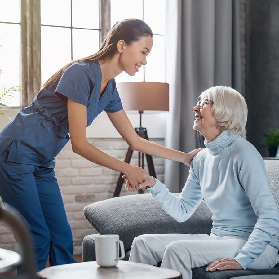 Registered nurse shakes hands with senior woman seated on a couch in a senior living facility