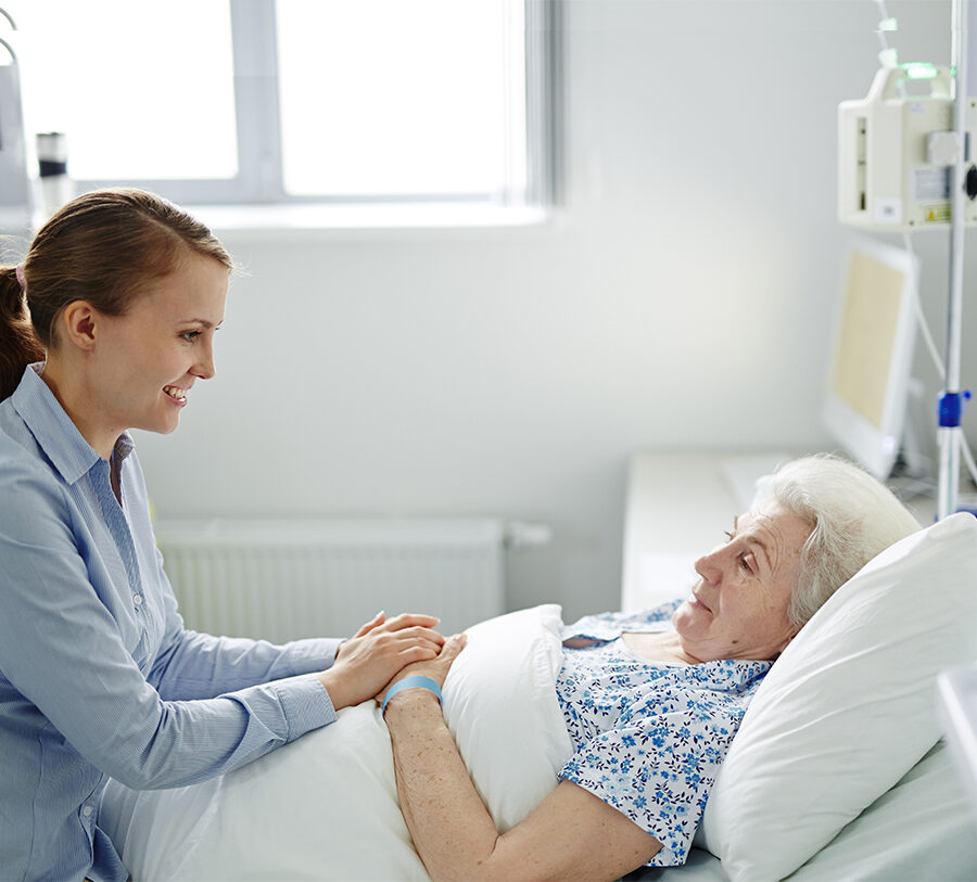 A senior woman laying in a bed receives hospice care while visiting with her daughter