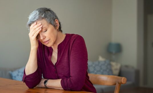 An older adult woman holds her head in her hand, a sign that she is stressed over her role as family caregiver, and may need to choose respite care.