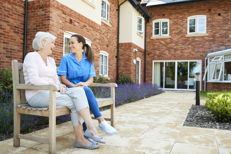 A care professional sits with a senior woman at an Assisted Living community that makes special considerations for those with Parkinson's disease.