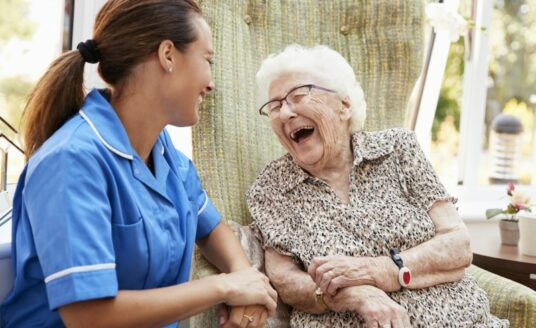 A senior woman and her professional caregiver chat at a memory care community.