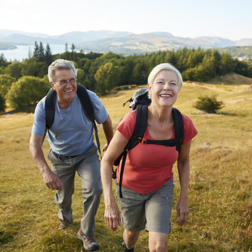 Senior aged man and woman hiking along a valley, reaping the benefits of exploring nature