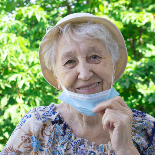 Older woman removing her face mask due to new covid guidelines for seniors