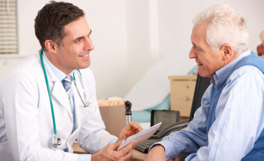a senior man talks to his doctor about being readmitted to the hospital