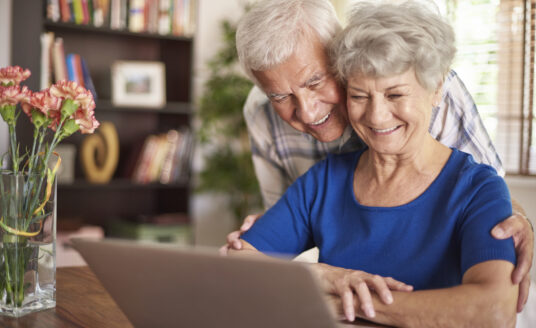 Senior couple looking at the computer, searching for an independent retirement community in St. Louis.