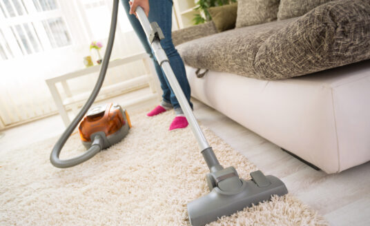 Vacuum running across carpet in seniors home for spring cleaning.