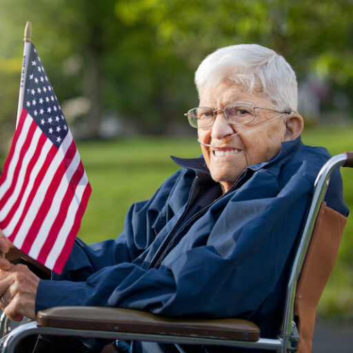 senior veteran sits in a wheelchair outside and holds an American flag