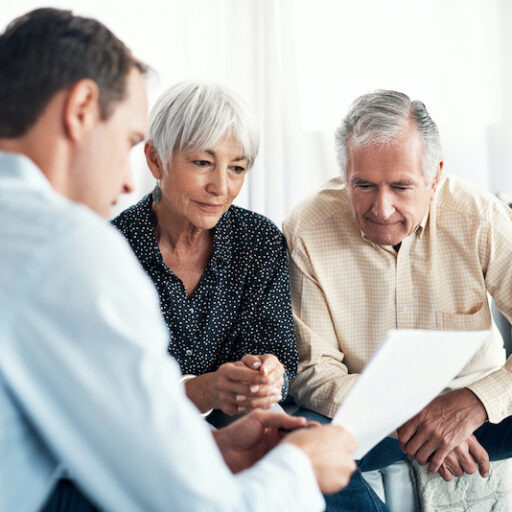 A young man discusses financial assistance for caregivers with a senior man and woman