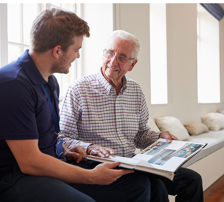 a young man offers memory support to a senior man with the help of a photo book