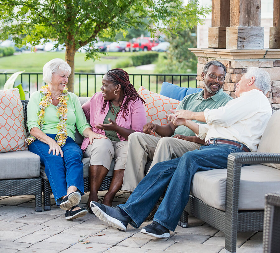 Two senior men and two senior women socialize outdoors on nice patio furniture