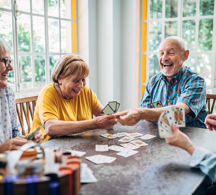 Three senior women and a senior man laugh over a game of poker