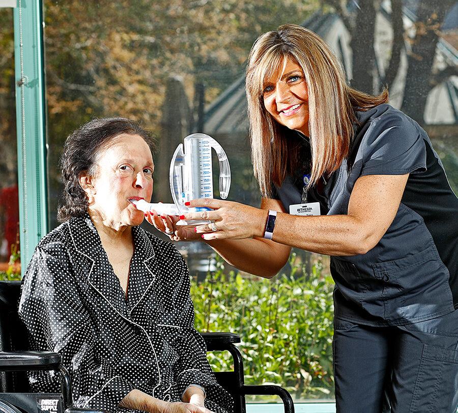 A female nurse provides respiratory therapy to a senior woman