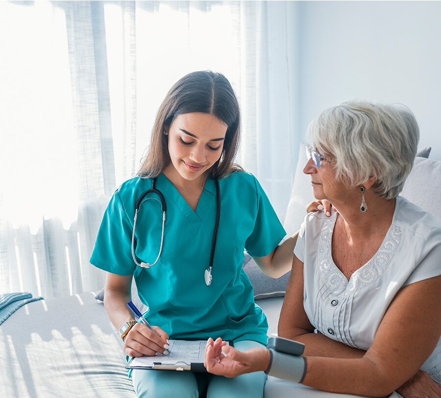 young skilled nursing professional checks the pulse of a senior woman and records the results on a clipboard
