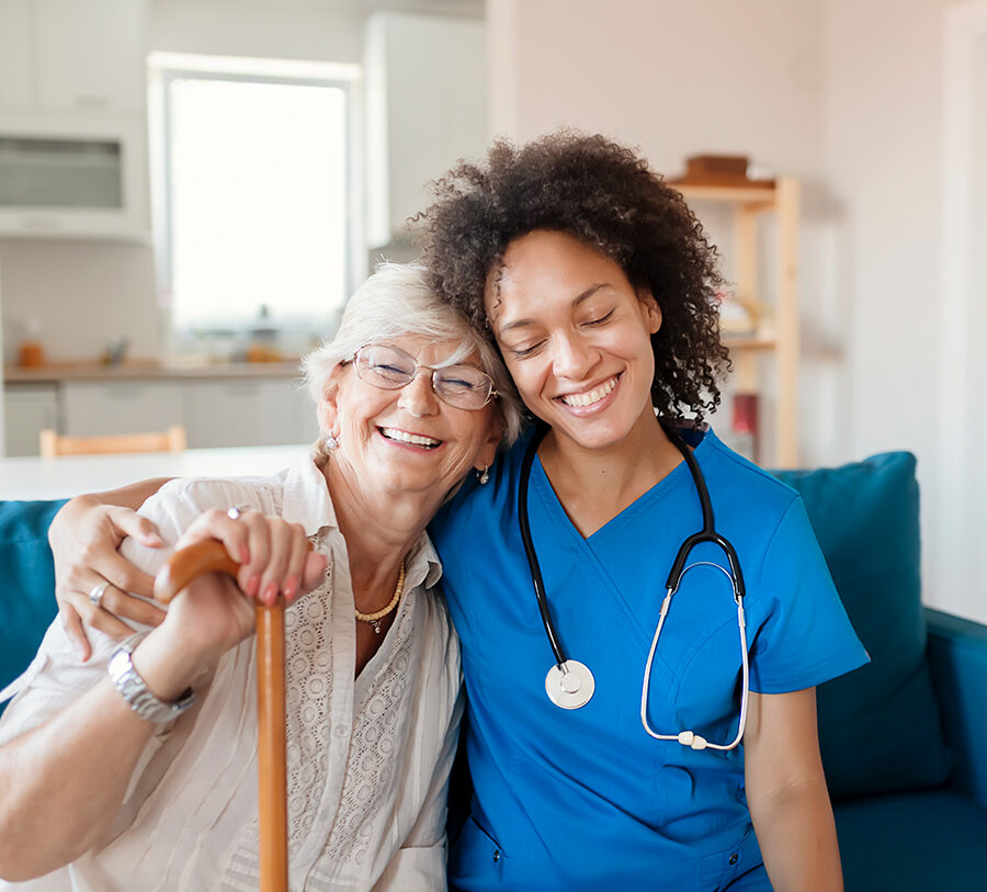 a young female nurse and a senior woman with a cane hug each other's shoulders and smile