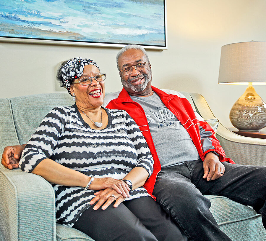 A senior man and woman pose and smile while seated on a loveseat