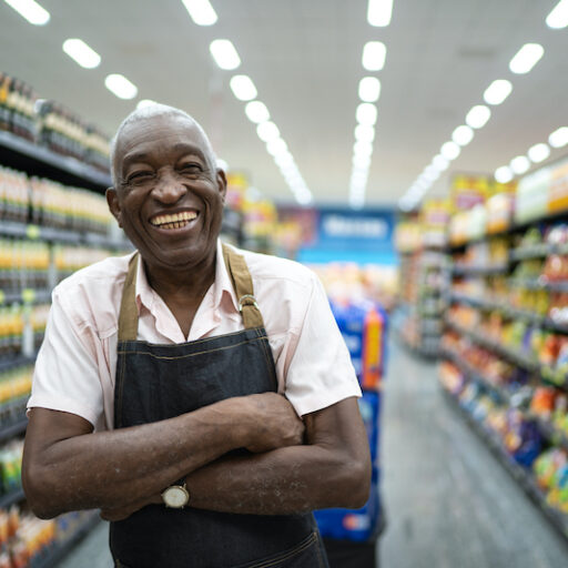 An older man stands in a grocery store aisle with an employee apron and arms crossed, representing the senior workforce