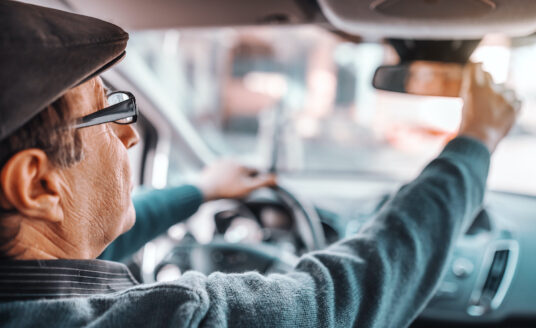 A male senior driver with a hat and glasses on adjusts his rear view mirror before driving.
