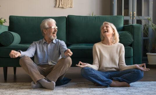 A senior man and a senior woman doing yoga on their living room floor