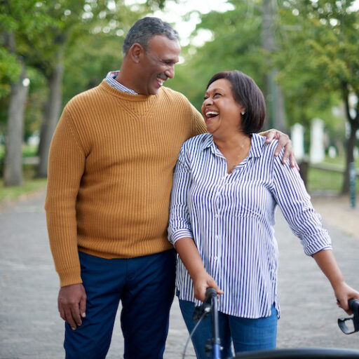 An older man and an older woman with a walker due to limited mobility take a stroll down a street lined with green trees