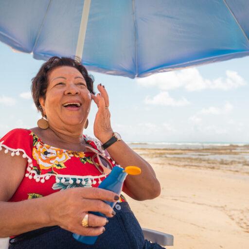 Senior woman applying sunscreen under an umbrella at the beach
