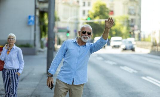 Senior man wearing sunglasses hails a ride on a sidewalk next to a busy street