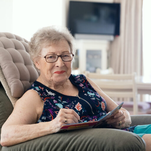 Older woman enjoying senior independence as she is seated in a comfortable recliner in her own home