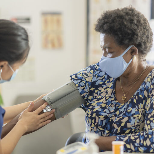 Senior woman wearing a face mask prevents hypertension by getting her blood pressure checked by a young female nurse
