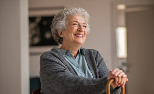 senior woman with decreased mobility smiles as she sits and holds her cane