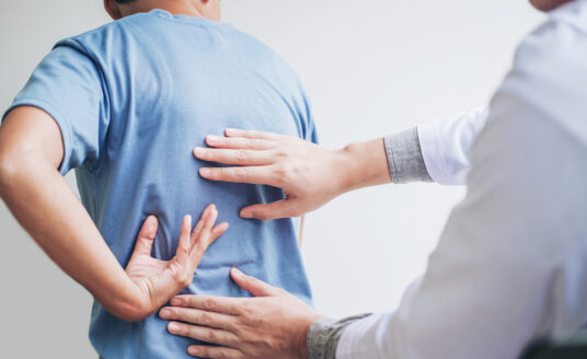 Senior man holding back as a doctor assesses the pain and condition