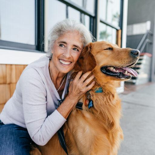 A senior woman hugs her golden retriever on a porch